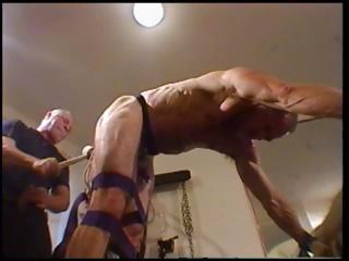 Dude is fastened up and bent over with his slaver abusing his ass