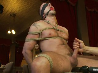 This guy is tied tight on that chair, blindfolded and ball gagged so he won't shriek or watch what happens to him. While his dick is tied real hard too, a dildo penetrates his chocolate hole and then his penis is released from the ropes so it could be rubbed. This guy enjoys the intense handjob and moans with fun