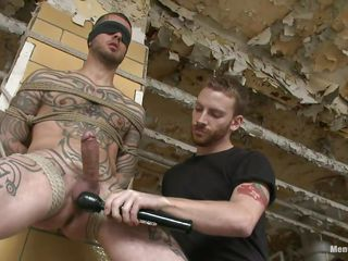 Tattooed man stays next to a wall all tied up. Some other man takes pictures with him, then his boyfriend begins licking and engulfing his very hard cock. His hairless balls are too being licked and then a vibrator comes to play with his head and balls. This chab is feeding himself and the other with pre-cum. Check it out!
